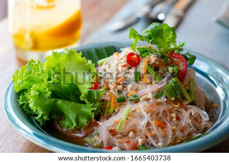 Selected focus, Spicy vermicelli salad on a table. Vermicelli spicy salad, with fresh vegetables and herbs. Spicy noodle salad, Spicy vermicelli salad (Yum Woon Sen). #1665403738