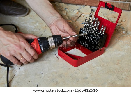 sets the Drill bit in the drill,hands take the drill bit and install in the electric drill #1665412516