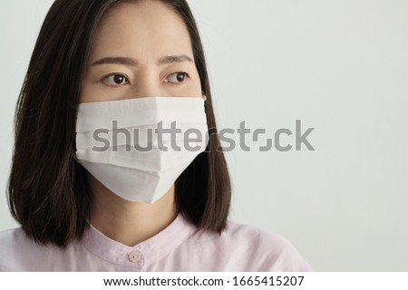 An ill asian woman wearing mask and sneezing stand on white background. Isolated picture of an ill asian woman. Isolated picture. #1665415207
