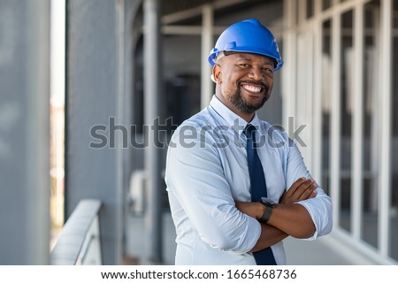 Portrait of african american man architect at building site looking at camera. Confident construction manager wearing hardhat. Successful mature civil engineer at construction site with copy space. #1665468736