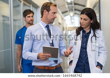Man and woman doctor having a discussion in hospital hallway. Doctor discussing patient case status with his medical staff after operation. Pharmaceutical representative showing medical report. #1665468742