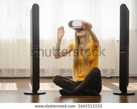Young woman wearing virtual reality goggles vr box with arms outstretched sitting on floor in living room, listening to music. Connection, technology, new generation and progress concept. #1665511552