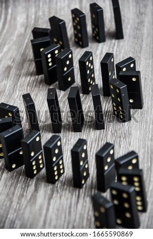 black dominoes on a light wooden table stand in a row, selective focus, Black old, vintage dominoes on a cardboard background. The concept of the game dominoes