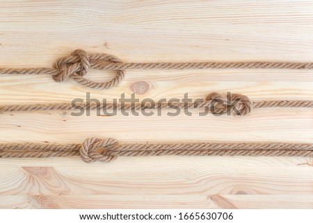 Marine knots used in yachting: figure eight knot, square knot, bowline knot. Nautical knots on wooden background. #1665630706