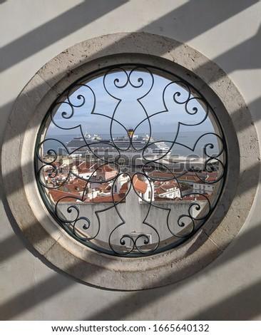 Cityview of lisboa rooftops and cruiseship through round vintage window