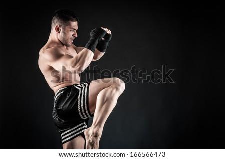 Sportsman kick boxer fighting against black background.  Royalty-Free Stock Photo #166566473