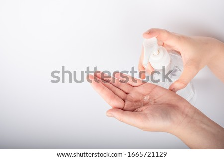 Woman hand using alcohol wash gel for cleaning sanitize gel pump dispenser on white background, health care concept #1665721129