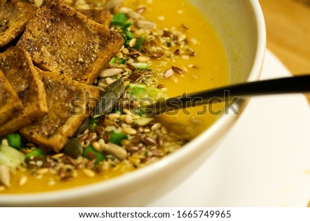 Cream soup with croutons and dill on white napkin, horizontal close up Royalty-Free Stock Photo #1665749965
