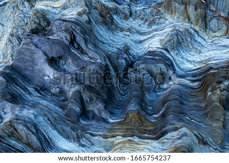 Detail of a rock with variants of blue. Rock full of curves and smooth cuts resulting from the erosive effect of sea. Close up rocks, texture dramatic and colorful erosional water formation. Royalty-Free Stock Photo #1665754237