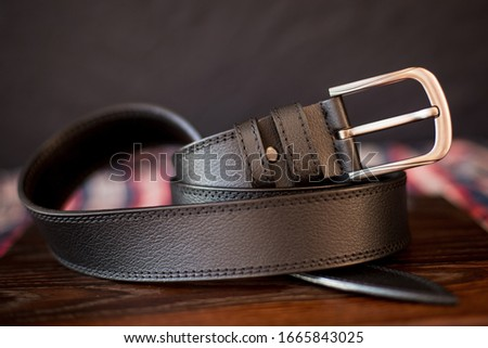 men's leather trouser belt in the background of dark wood, men's  fashion accessories closet. Genuine leather, handmade Royalty-Free Stock Photo #1665843025
