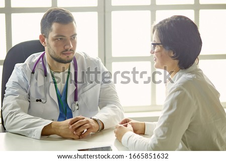 Young doctor talking to a patient in the office #1665851632