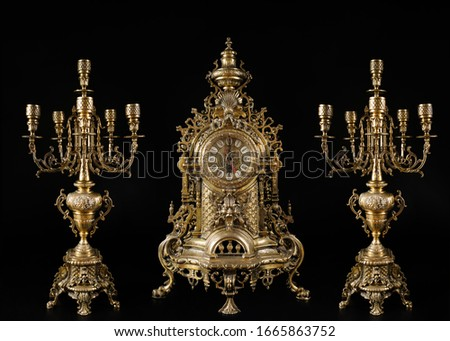 vintage gold watch with candelabra on black background, bronze clock and candelabra, gold candlesticks and clock, antique clock and candlesticks, vintage clock with chandeliers on a black background #1665863752