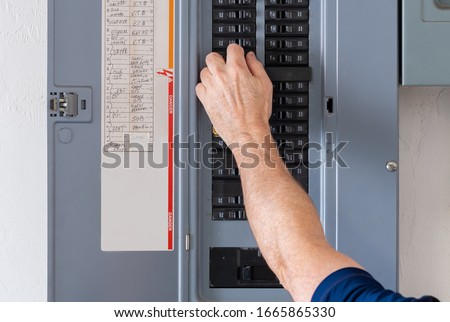 Resetting tripped breaker in residential electricity power panel. Male electrician turning off power for electrical outlet at circuit breaker box. Royalty-Free Stock Photo #1665865330