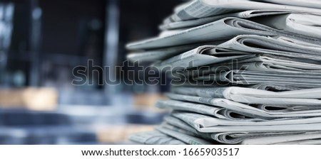 Pile of fresh newspapers on blur background Royalty-Free Stock Photo #1665903517