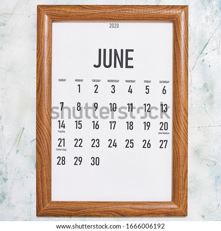 June 2020 monthly calendar placed in the wooden picture frame. View from above