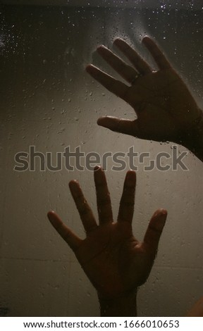 Blurry hand abstraction. Shadow hands of the woman behind frosted glass. Halloween background #1666010653