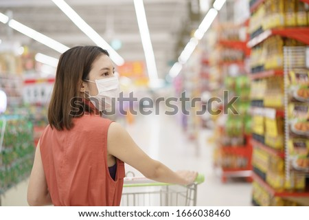covid-19 spreading outbreak. Woman in medical protective mask panic buying food. Fear of coronavirus. #1666038460