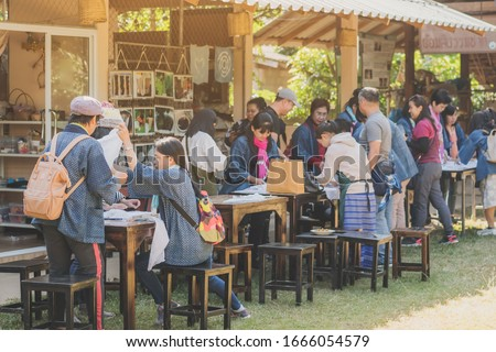 LAMPHUN THAILAND - DECEMBER 12 :  Unidentified Thai female tourists learn to make tie-dye clothes on December12,2019 at Karen village in Lamphun, Thailand #1666054579