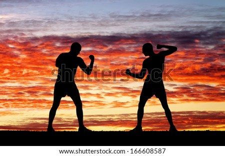 Silhouettes of two fighters on sunset fiery background  Royalty-Free Stock Photo #166608587