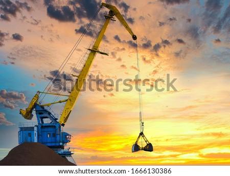 Yellow crane in cargo port translating coal. Industrial scene Royalty-Free Stock Photo #1666130386