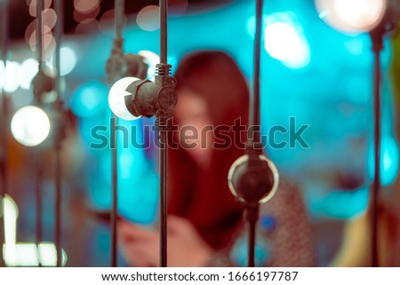 Blurred picture of a woman on bright Bokeh light on chair decoration in Outdoor Festive Market in Lush Lava color toned