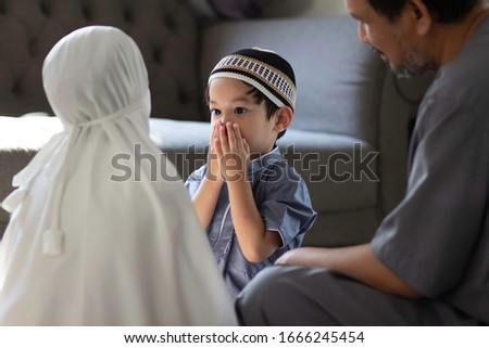Image of Asian Muslim family in traditional costume.Muslim father with kids in their house after pray to God.Concept of Muslim people in Ramadan holy month. #1666245454