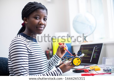 Portrait Of Female Teenage Pupil Building Robot Car In Science Lesson Royalty-Free Stock Photo #1666265311