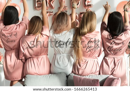 Bride with girlfriends in silk robes at a bachelorette party. Royalty-Free Stock Photo #1666265413