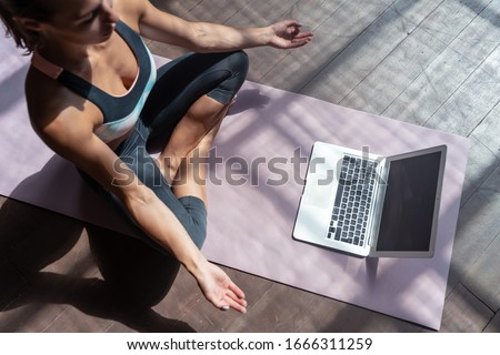 Top view young sporty slim woman coach internet video online training hatha yoga instructor modern laptop screen meditate Sukhasana posture relax breathe easy seat pose gym healthy lifestyle concept. #1666311259