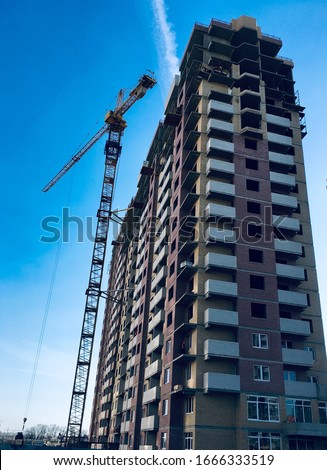 A tall house is built by a contractor with a crane. Photo of the house on a background of blue cloudless sky. Construction site for demounting the construction industry #1666333519
