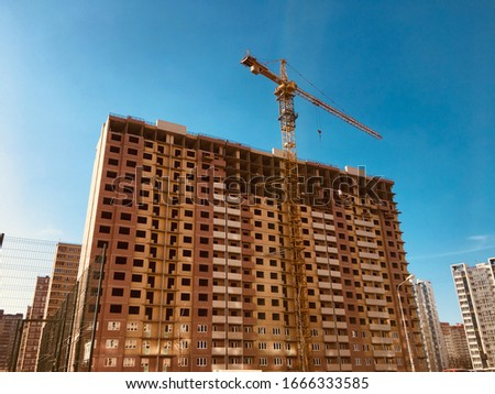 A tall house is built by a contractor with a crane. Photo of the house on a background of blue cloudless sky. Construction site for demounting the construction industry #1666333585