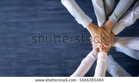 Close up top view of young business people putting their hands together. Stack of hands. Unity and teamwork concept. Royalty-Free Stock Photo #1666381684