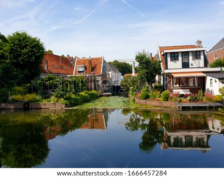Beautiful Edam houses with reflection on the river.  #1666457284