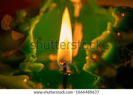 macro image of a  green christmas candle flame burning