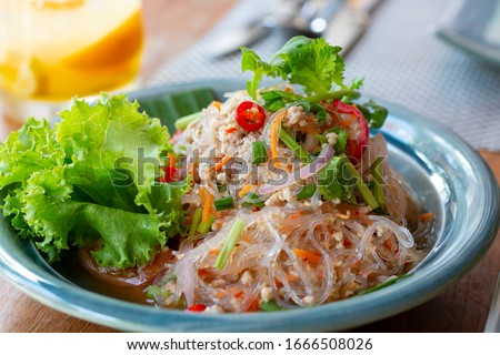Selected focus, Spicy vermicelli salad on a table. Vermicelli spicy salad, with fresh vegetables and herbs. Spicy noodle salad, Spicy vermicelli salad (Yum Woon Sen). #1666508026