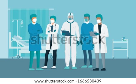 Professional doctors and nurses posing together in a hospital ward and wearing protective suits, virus outbreak emergency concept Royalty-Free Stock Photo #1666530439