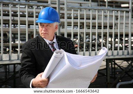 Contractor. Contractor examining blueprints at a construction site. Construction Site Supervisor or Contractor with Blue Prints at a work site. Building and Homes being built world wide. United States #1666543642