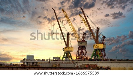 Massive blue, orange and yellow cranes in harbour Royalty-Free Stock Photo #1666575589