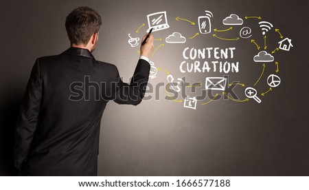 businessman drawing social media icons with CONTENT CURATION inscription, new media concept