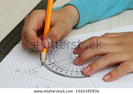 Closeup child's hands measuring angle by protractor.