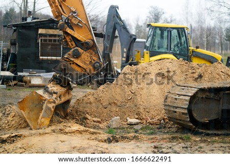 Excavators machine in construction site on sky background. Royalty-Free Stock Photo #1666622491