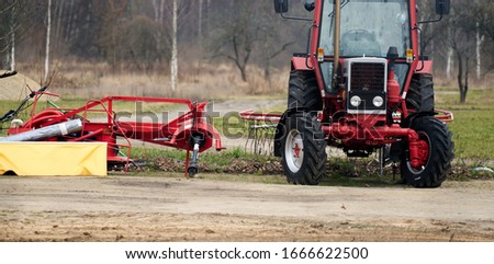 Small scale farming with tractor and plow in field. Royalty-Free Stock Photo #1666622500