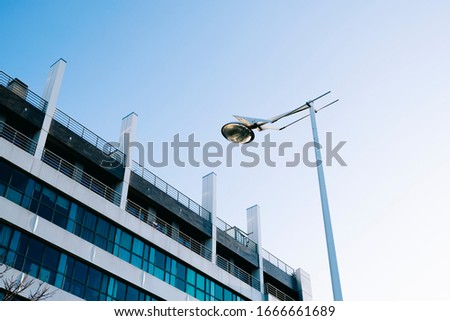 A modern white building with bluish glass and a white lamppost with blue sky on sunny day #1666661689