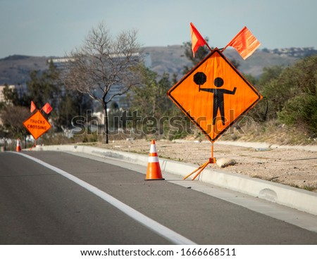 Orange diamond road sign with graphic of person holding a stop sign at a construction site. The sign has ornage flags on top and there is a sign reading Trucks Crossing in the distance
