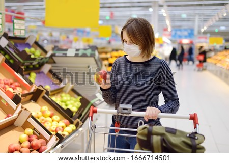 Young woman wearing disposable medical mask shopping in supermarket during coronavirus pneumonia outbreak. Protection and prevent measures while epidemic time. #1666714501