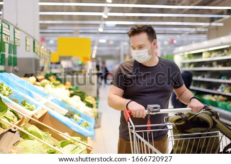 Man wearing disposable medical mask shopping in supermarket during coronavirus pneumonia outbreak. Protection and prevent measures while epidemic time. #1666720927