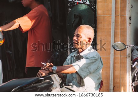Da Lat, Vietnam - February 28, 2020: Outdoors portrait shot of an old Vietnamese mechanic, wearing a dirty white shirt, sitting alone, leaning back against the wall, smoking a cigarette to relax #1666730185