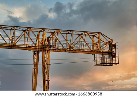 Industrial construction cranes and building silhouettes over sun at sunrise. Royalty-Free Stock Photo #1666800958