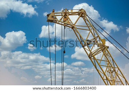 blue sunset sky after five big high cranes under a new construction site of high-rise building against blue sunset sky Royalty-Free Stock Photo #1666803400