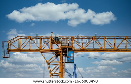 Industrial construction cranes and building silhouettes over sun at sunrise. Royalty-Free Stock Photo #1666803490